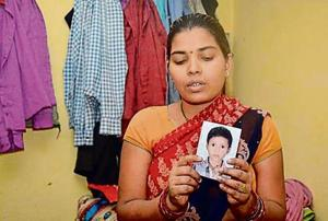 Anita,  mother of 13-year-old Kishan who has been missing for nearly a month now, holds his picture.