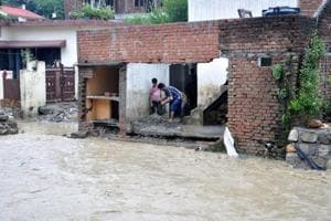 People remove silt from a house collapsed as raising water of Rispana river entered it at Tarla Adhoiwala in Dehradun on Wednesday.