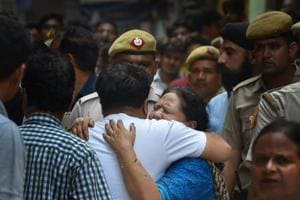 Relatives mourn as Police carries out the investigation, after 11 members of a family- four men, three women and four girls- were found hanging from an iron grill in a house, in Burari area of New Delhi on Sunday, July 1, 2018.