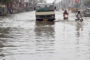 Vehicles wade through waterlogged streets during rains in Jaipur on Thursday.