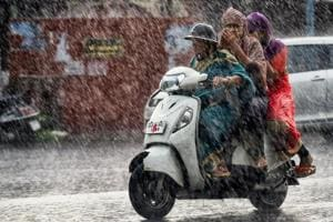 Commuters make their way across a street during heavy rain in Ahmedabad.