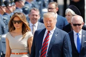 US President Donald Trump (C) and First Lady Melania Trump (L) walk on the tarmac with US Ambassador to the United Kingdom Woody Johnson (R) as they disembark Air Force One at Stansted Airport, north of London on Thursday as he begins his first visit to the UK as US president.