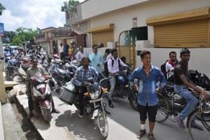 People wait for traffic restrictions to end on a road in Dehradun during vice-president MVenkaiah Naidu's visit to the city on Saturday.