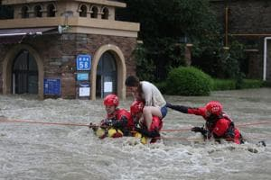 Firefighters rescue a stranded woman on a flooded street, following heavy rainfall in Chengdu, Sichuan province, China July 11, 2018.