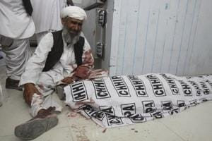 A man mourns next to a body of his family member killed in a bomb blast, in Quetta, Pakistan.