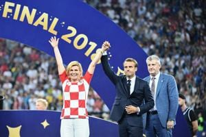 French President Emmanuel Macron (C) and Croatian President Kolinda Grabar-Kitarovic acknowledge the public after the Russia 2018 World Cup final football match between France and Croatia at the Luzhniki Stadium in Moscow.