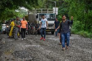 Residents fill potholes on Susgaon road in Pune on Sunday, July 15.