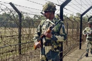 Border Security Force (BSF) personnel patrol along the India-Bangladesh border fence at Yakub Nagar village ahead of Republic Day in Dharmanagar.