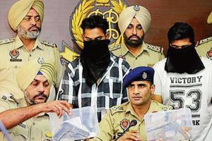 SSP Kuldeep Singh Chahal and other officers with two of the arrested accused and seized pistols at a press conference in Mohali on Monday.