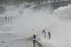 People enjoy the high tide at Marine Drive in Mumbai, India, on Sunday, July 15, 2018.