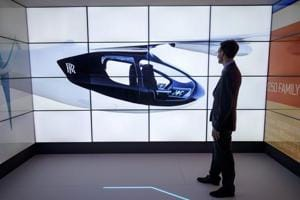 A man poses alongside screens presenting the Rolls-Royce EVTOL air taxi concept during the Farnborough Airshow.