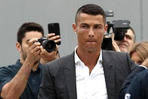 Portuguese footballer Cristiano Ronaldo surrounded by photographs looks on as he greets supporters outside the Juventus medical center at the Alliance stadium in Turin on July 16, 2018. Cristiano Ronaldo arrived in Turin ahead of his official unveiling as Juventus