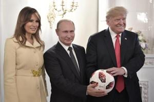 US First Lady Melania Trump, left, Russian President Vladimir Putin, centre, and US President Donald Trump pose with a football after a press conference following their meeting at the Presidential Palace in Helsinki, Finland, July 16