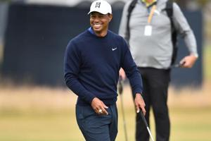 US golfer Tiger Woods smiles as he putts on the 9th green during a practice round at The 147th Open golf Championship at Carnoustie, Scotland.