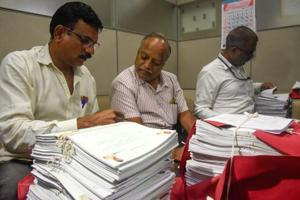 Officials checking affidavits of police and government officials submitted by advocate Shishir Hire regarding the Bhima Koregaon violence at council hall in Pune on Monday.