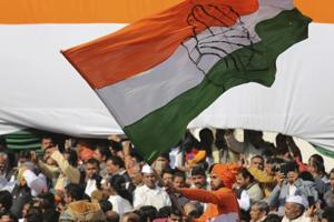 A Congress party worker waves the party flag during a function in New Delhi.