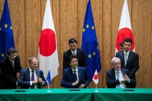 Japanese Prime Minister Shinzo Abe (C) signs an agreement with European Council President Donald Tusk (L) and European Commission President Jean-Claude Juncker (R) at the Prime Minister