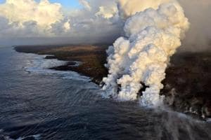 Laze plumes rising where lava pours into the sea on the south margin of the fissure 8 flow of the Kilauea volcano in Hawaii.