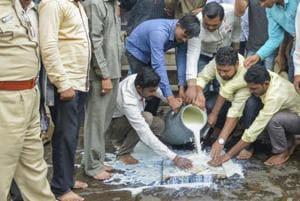 Swabhimani Shetkari Sanghatana activists pour milk in front of a temple in Karad, Maharashtra, on Monday.