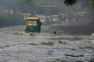 Vehicles wade across a waterlogged street after monsoon rain in New Delhi, on Monday.
