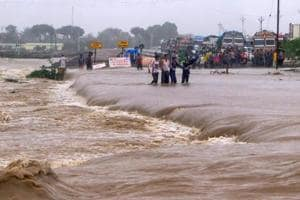 People make way through flood waters on the Una-Veraval highway after heavy rains, in Una town of Gir Somnath district on Tuesday, July 17, 2018.