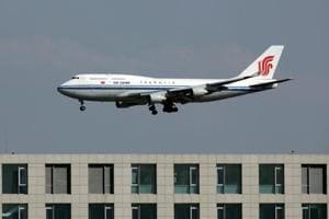 An Air China Boeing 747 passenger jet lands at the Beijing Capital Airport near Langham Place Hotel.