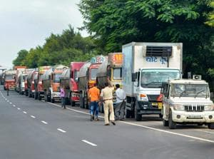 A police vehicle accompanies milk tankers on their way to Mumbai on Pune-Bangalore National Highway.
