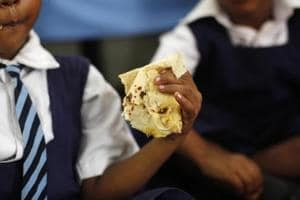 A schoolgirl eats her free mid-day meal, distributed by a government-run primary school, in New Delhi July 5, 2013.