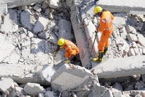 National Disaster Response Force (NDRF) rescue workers retrieve a dead body from the debris of the buildings, at Shahberi village in Greater Noida.
