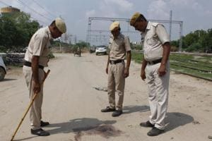 Police officials inspect the site where 37-year-old property dealer Mahesh Kumar Yadav was shot dead by five assailants in Sarai Alawardi near Palam Vihar at around 6: 30 am in Gurugram on Wednesday, July 18, 2018.