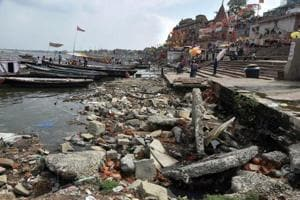 People stand near the dried out Assi Ghat of the Ganga river in Varanasi on June 28.