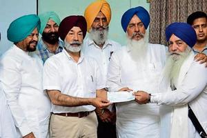 Amritsar deputy commissioner Kamaljeet Singh Sangha (second from left) and Patti MLA Harminder Singh Gill (second from right) handing over a cheque to a Jodhpur detainee in Amritsar on Friday as Attari MLA Tarsem Singh DC (left) looks on.