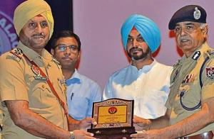 Punjab DGP Suresh Arora (right) honouring inspector Gurmel Singh for helping addicts give up drugs, during a programme in Doraha on Friday.