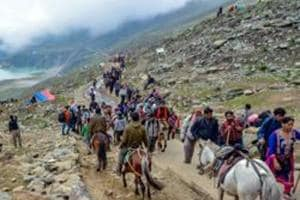 Security personnel look on as a batch of pilgrims are on their way towards the holy cave shrine of Amarnath, in Sheshnag Lake.