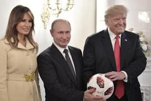 U.S. First Lady Melania Trump, left, Russian President Vladimir Putin, center, and U.S. President Donald Trump, pose with a soccer ball after a press conference following their meeting at the Presidential Palace in Helsinki, Finland, Monday, July 16, 2018.