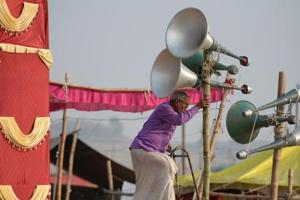 A worker adjusts loudspeakers at a camp during the Magh Mela festival in Allahabad on January 6, 2018.