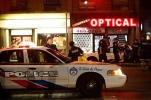 Toronto Police officers walk the scene at Danforth St. at the scene of a shooting in Toronto, Canada.