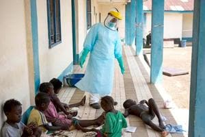 A health official dressed in protective gear examines children suffering from the Ebola virus.