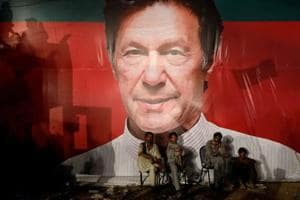 Workers, who set up the venue, sit under a wall with a billboard displaying photo of Imran Khan, chairman of the Pakistan Tehreek-e-Insaf (PTI), political party, as they listen to him during a campaign rally ahead of general elections in Karachi, Pakistan.