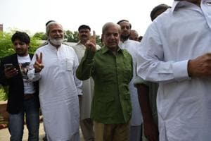 Shabaz Sharif (C), the younger brother of ousted Pakistani Prime Minister Nawaz Sharif and the head of Pakistan Muslim League-Nawaz (PML-N), stands in a queue before casting his vote during Pakistan
