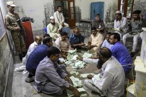 Polling agents count votes after polls close at a polling station in Lahore, Pakistan.