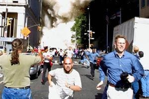 This September 11, 2001 file photo shows pedestrians running from the scene as one of the World Trade Center Towers collapses in New York City following a plane crash on the twin towers.