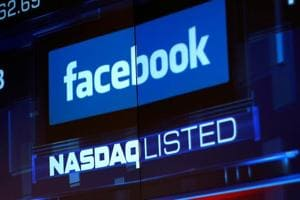 Monitors displays the Facebook, Inc. stock during morning trading at the NASDAQ Marketsite in New York, US.  Facebook shares tumbled by more than 20 per cent on Wednesday after the social media network's revenue and user growth fell short of investor expectations.
