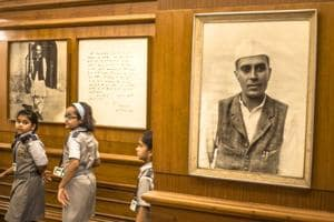 Children walk past a photograph of Jawaharlal Nehru at the Nehru Memorial Museum in Delhi.