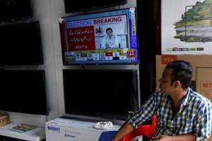 A shopkeeper looks on a screen, displaying the cricket star-turned-politician Imran Khan, chairman of Pakistan Tehreek-e-Insaf (PTI), in a televised speech a day after the general election, at a market in Karachi, Pakistan July 26, 2018.
