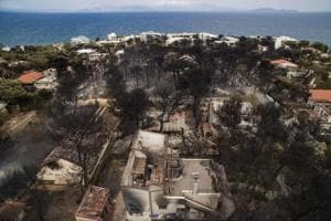 An aerial view shows burnt houses following a wildfire in the village of Mati, near Athens, .