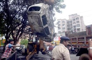 Police take away the car that was burnt by protesters during the Maratha agitation in Kopar Khairane on Wednesday.