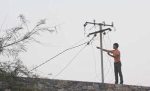A man fiddles with a power line.