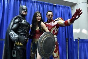 Fans dressed as Batman (left), Wonder Woman (centre), and Iron Man (right) attend day one of Comic-Con International, San Diego, July 19, 2018