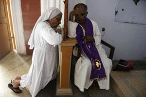 An Indian Catholic Priest(R) hear the confessions of penitents at a confessional cabinet at Saint Mary
